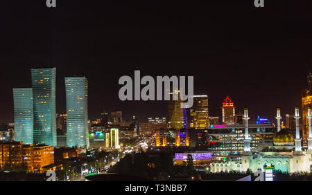 Night view of Northern Lights apartment buildings and Nur Mosque in the city center, Astana, Kazakhstan - Stock Photo