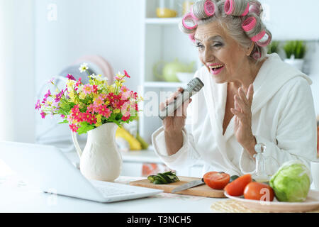 Senior woman in hair rollers singing karaoke with laptop at home - Stock Photo