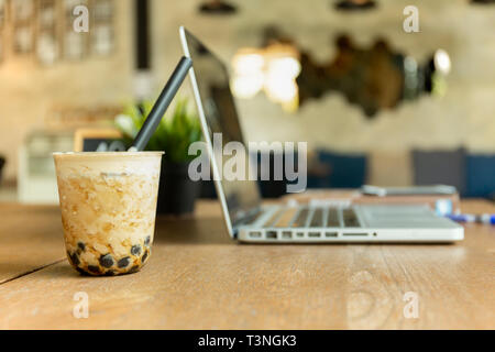 Pearl milk iced tea with laptop on wooden table in cafe. - Stock Photo