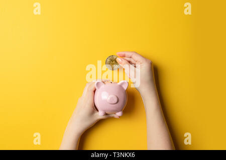 Female hand with bitcoin coin put in a piggy bank - Stock Photo