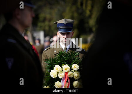 Warsaw, Poland. 10th Apr, 2019. A soldier holds a wreath at the Powazki Military Cemetery in Warsaw, Poland, on April 10, 2019. Poland's political leaders are leading throughout Wednesday a series of commemorative events to mark the ninth anniversary of the Smolensk plane crash, which killed 96 people, including former Polish President Lech Kaczynski. Credit: Jaap Arriens/Xinhua/Alamy Live News - Stock Photo