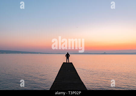 Man silhouetted standing on breakwater which extends out to sea at sunrise - Stock Photo