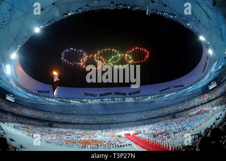 (190411) -- BEIJING, April 11, 2019 (Xinhua) -- Photo taken on Aug. 8, 2008 shows the fireworks in the shape of Olympic rings during the opening ceremony of the Beijing Olympic Games held in the National Stadium, also known as the Bird's Nest, in north Beijing, China. From sending athletes to Helsinki Summer Olympic Games for the very first time in 1952 to winning the bid to host 2022 Winter Olympic Games in 2015, the People's Republic of China went through a remarkable history of sports, including successfully hosting the 2008 Summer Olympic Games and preparing for the upcoming 2022 Winter O - Stock Photo