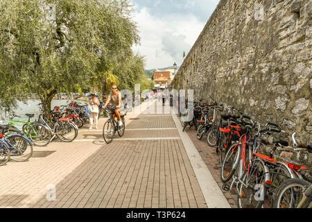 GARDA, LAKE GARDA, ITALY - SEPTEMBER 2018: Row of bicycles parked against a wall on the promenade in Garda on Lake Garda. - Stock Photo