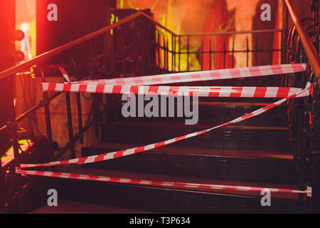 Danger tape waving in the wind in front of empty house ready to be demolished - Stock Photo