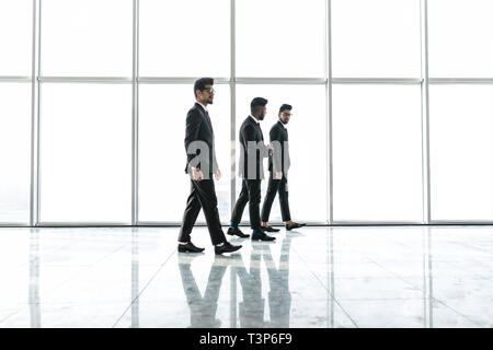 Confident business partners walking down in office building and talking about new project. - Stock Photo