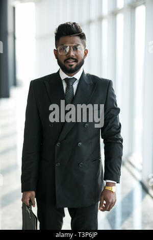 Full length shot of a stylish young businessman wearing a modern suit, who is a high achiever, standing on the top floor of an office building looking - Stock Photo
