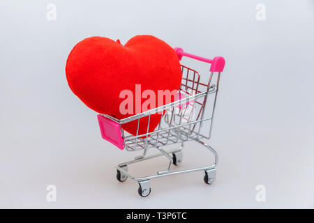 Sale buy mall market shop consumer concept. Simply minimal design with small supermarket grocery push cart for shopping toy with wheels and heart isol - Stock Photo