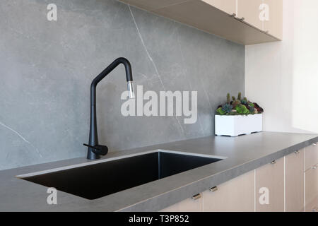A black sink and matt finish black faucet set against a grey countertop and backsplash made of porcelain slabs that mimic the natural look of stones,  - Stock Photo
