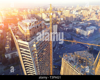 Rood of high tower building construction site. Bug industrial crane. Aerial drone view. Metropolis city development - Stock Photo