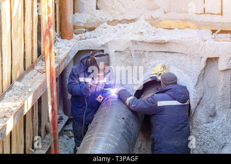 Welder welding water or gas steel pipeline with assistant worker in trench. City underground utilitites renewal and replacemen - Stock Photo