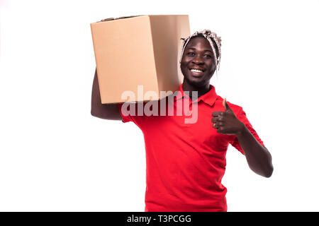 Delivery Concept - Portrait of Happy African American delivery man holding a box package and showing thumbs up. Isolated on Grey studio Background. Co - Stock Photo