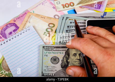 Denominations of the Ukrainian hryvnia of the bills in the under the bills a fragment of the US dollar bill. - Stock Photo