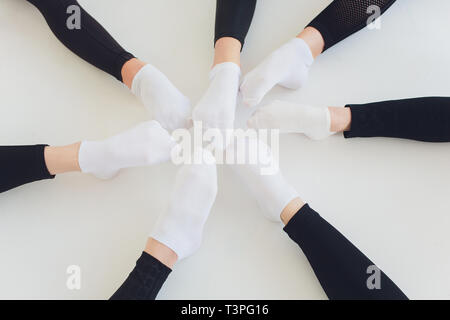 Ballet dancer tying ballet shoes. Close up ballet girl putting on her pointe shoes sitting on the floor, blurred background. - Stock Photo
