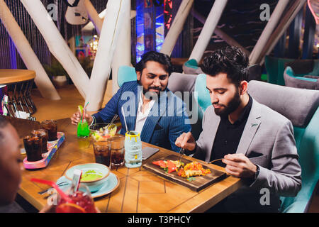 Two Man In Bar Hold Glasses Sit At Counter, Drinking cocktail, Cheerful Friends Meeting Bar Communicate Talking. - Stock Photo