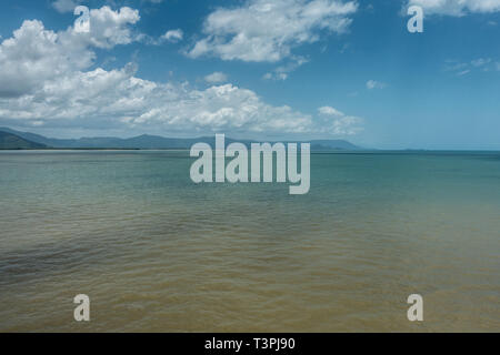 Cairns, Australia - February 17, 2019: Shallow and calm Coral Sea water in front of the town. Horizon of mountains north of the city part of Kuranda N - Stock Photo