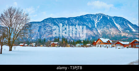 Panorama of Obertraun with numerous wooden cottages and large snowbound field on the foreground, Salzkammergut, Austria.