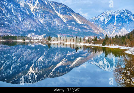 Reflection in mirror surface of Hallstatter see (lake) of the snowy bank of Obertraun village, covered with coniferous forest and Dachstein Alps on th - Stock Photo