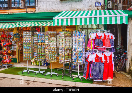 HALLSTATT, AUSTRIA - FEBRUARY 21, 2019: The stands with magnets, postcards, folk costumes and other souvenirs in front of the tourist shop, on Februar - Stock Photo