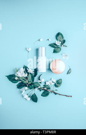 Natural organic cosmetics on blue background in a frame of flowers. Spa concept - Stock Photo