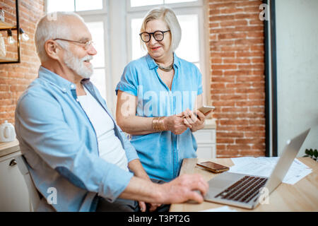 Beautiful senior couple in blue shirts sitting together with laptop on the kitchen at home - Stock Photo