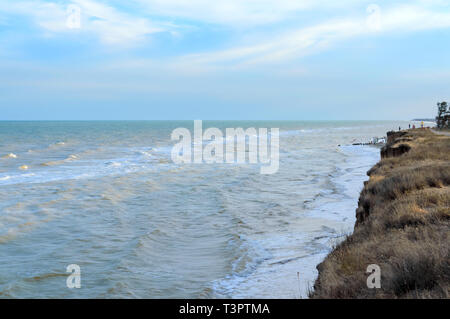 Top view on the sea and the waves crashing on the shore in the sunlight. Beach on the coast. - Stock Photo