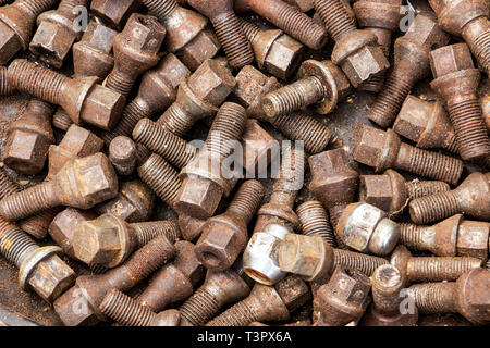 Used old oily wheel bolts, wheel nuts, texture background - Stock Photo
