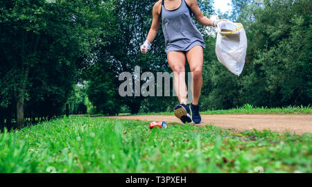 Girl with garbage bag doing plogging - Stock Photo