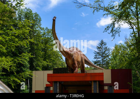 big dinosaur in a forest, guarding a entrance - Stock Photo