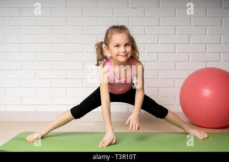 beautiful little child doing gymnastics exercises isolated