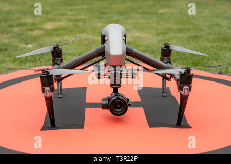 A DJI Inspire 2 professional drone on the ground on an orange landing mat with grass surrounding - Stock Photo