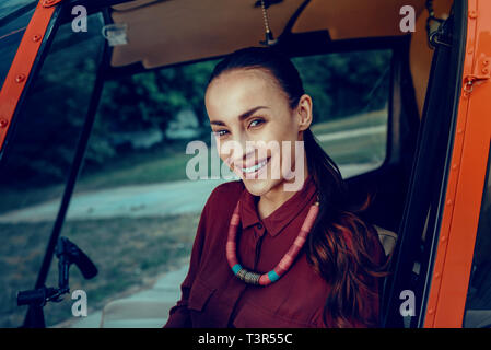 Dark-haired attractive woman with bright jewelry staying in helicopter - Stock Photo