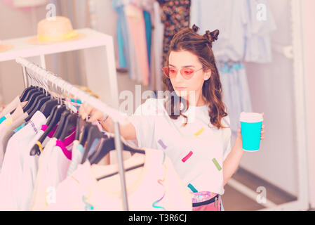 Stylish girl choosing new clothes in the atelier - Stock Photo