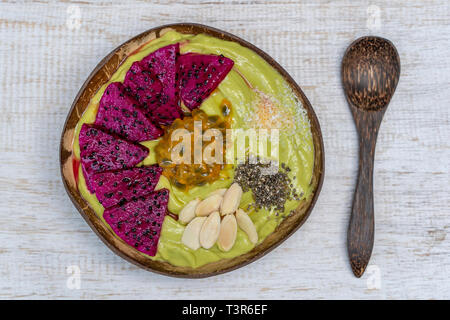 Green avocado smoothie in coconut bowl with dragon fruit, passion fruit, almond flakes, coconut chips and chia seeds for breakfast , close up. The con - Stock Photo