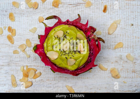 Green avocado smoothie in dragon fruit skin with almond flakes and chia seeds for breakfast , close up. The concept of healthy eating, superfood . Bal - Stock Photo