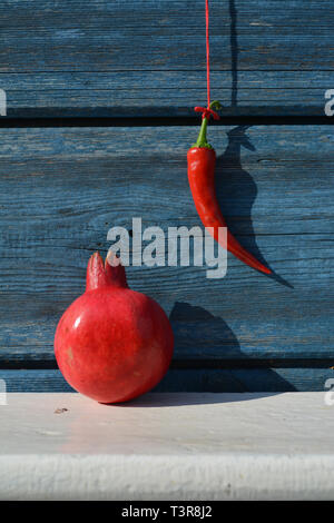 Red hot chili pepper hanging on wooden wall and pomegranate on white shelf - Stock Photo