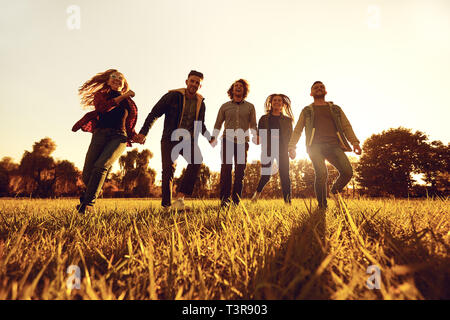 A group of young people running through the grass in the park at sunset.  - Stock Photo