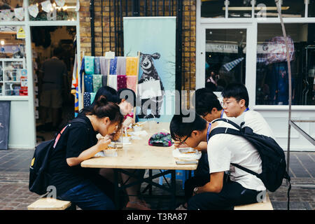 London, UK - July 23, 2018: Chinese tourists eating out on the Greenwich street market in London - Stock Photo