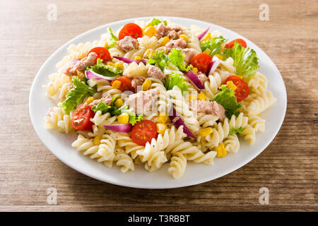Pasta salad with vegetables and tuna on wooden table - Stock Photo