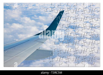 Airplane wing above the clouds in jigsaw puzzle shape - concept image which can mean: overcome fear of flying or solutions to air sickness or plan the - Stock Photo