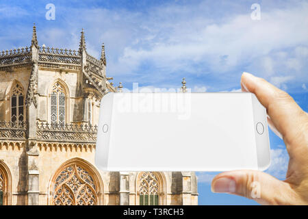 Hand holding a blank smartphone with a picture of Batalha cathedral in Portugal (Europe) - 3D render with copy space - Stock Photo