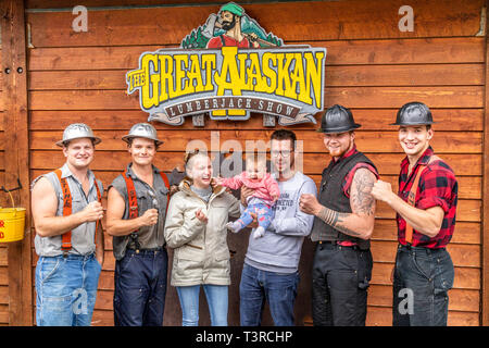 A young family with the lumberjacks after the show at the Great Alaskan Lumberjack Show in Ketchikan, Alaska USA - Stock Photo