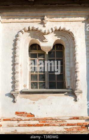 Veliky Novgorod, Russia. Medieval window decorated with arches and stucco at the facade of Resurrection Cathedral of Derevyanitsky monastery - Stock Photo