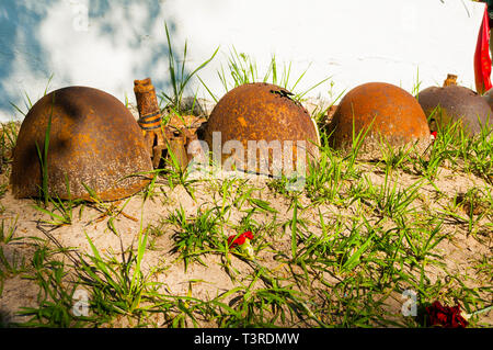 Soviet military helmets with flowers and wreath at the cemetery of fallen soldiers during World War II. Veliky Novgorod, Russia - Stock Photo