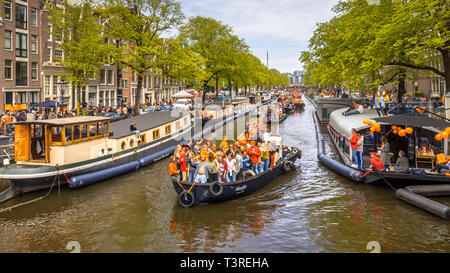 AMSTERDAM, THE NETHERLANDS - APRIL 27 2018: Canal boat parade on Koningsdag Kings day festivities. Birthday of the king. - Stock Photo