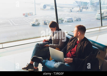 Elegant business couple working with laptop and phone sitting at the waiting hall in the airport. Business travel concept. - Stock Photo