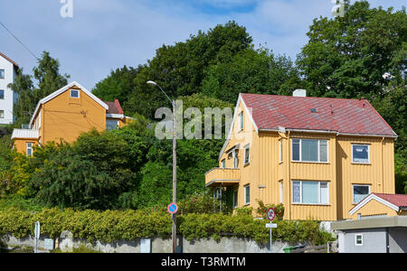 Typical brightly coloured wooden clad Norwegian Houses built on to a steep hill and surrounded by lush vegetation in the town of Kristiansund, Norway. - Stock Photo