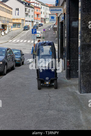 A Blue covered Norwegian Mobility scooter parked outside a bank on the the pavement of a steep hill on a summers day in Kristiansund, Norway. - Stock Photo