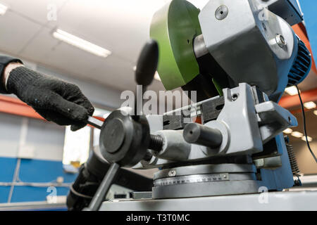 worker cuts a piece of material with a circular saw machine. Industrial engineer working on cutting a metal and steel with compound mitre saw with - Stock Photo
