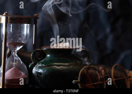 Old hourglass and spectacles near extinguished candle with smoke - Stock Photo